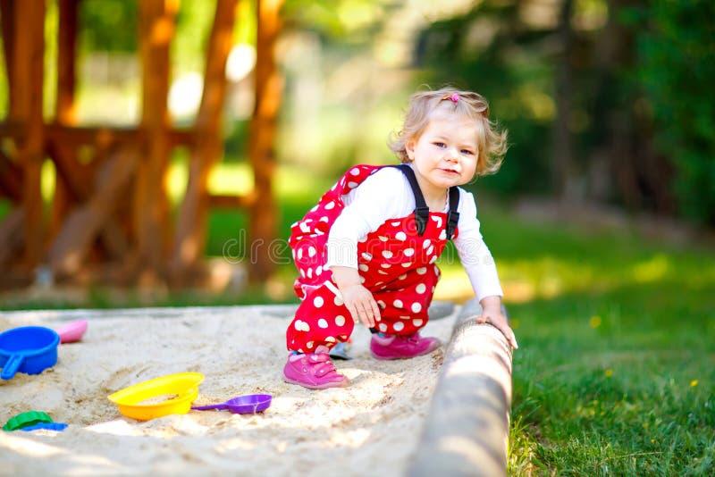 Gullig litet barnflicka som spelar i sand på utomhus- lekplats Härligt behandla som ett barn i byxa för rött gummi som har gyckel royaltyfri bild