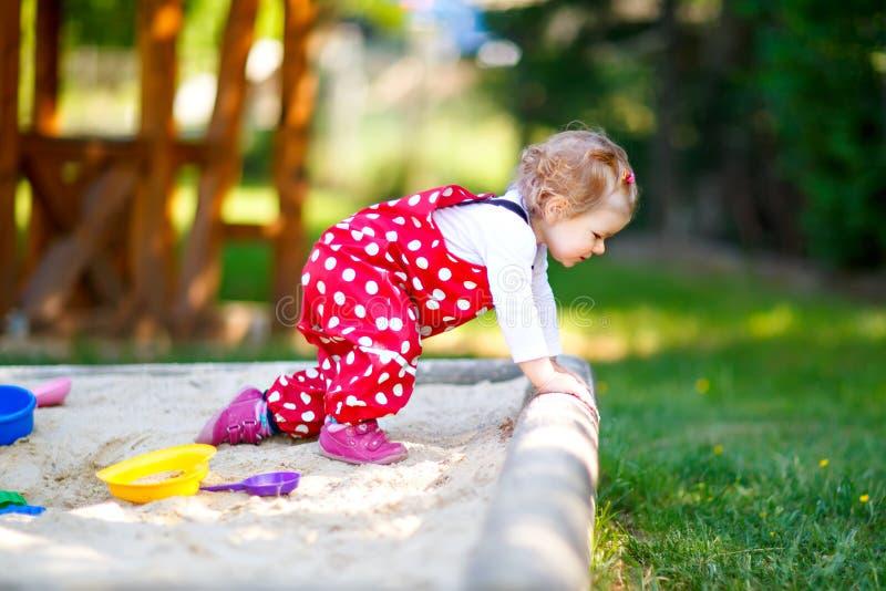 Gullig litet barnflicka som spelar i sand på utomhus- lekplats Härligt behandla som ett barn i byxa för rött gummi som har gyckel arkivbild