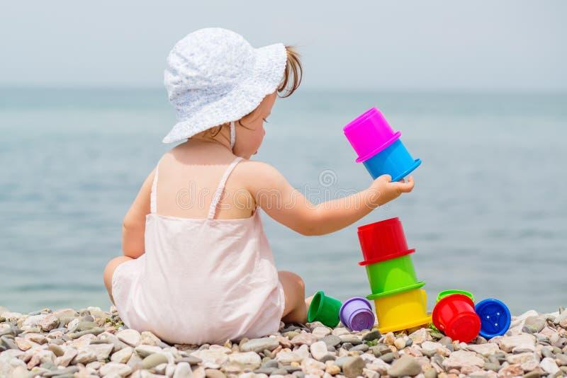 Gullig litet barnflicka som spelar med färgrik leksaker royaltyfri bild