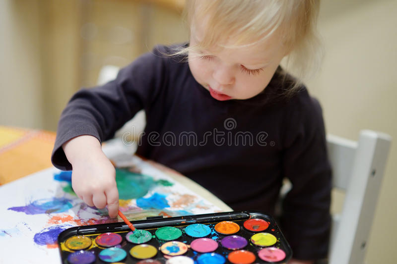 Gullig litet barnflickateckning med målarfärger i förträning arkivfoto