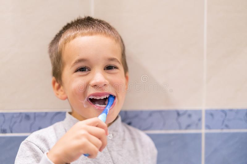 Gullig litet barnpojke som borstar hans tänder i badrummet Unge som lär hur man blir sunt bakgrund suddighetdde den skyddande pil arkivbild