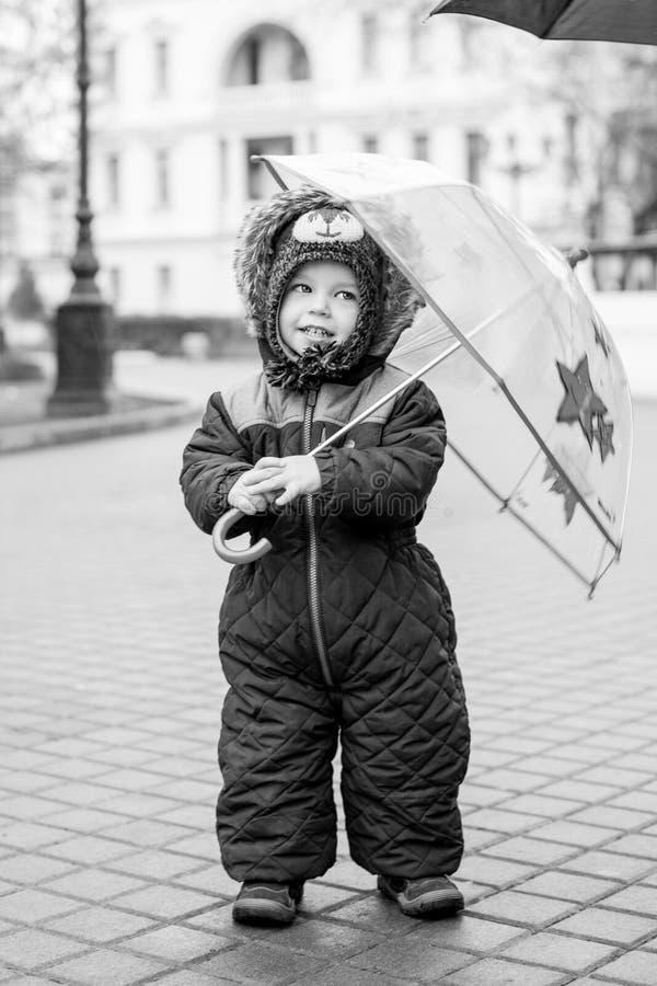 Gullig litet barnpojke som går i stad arkivbild