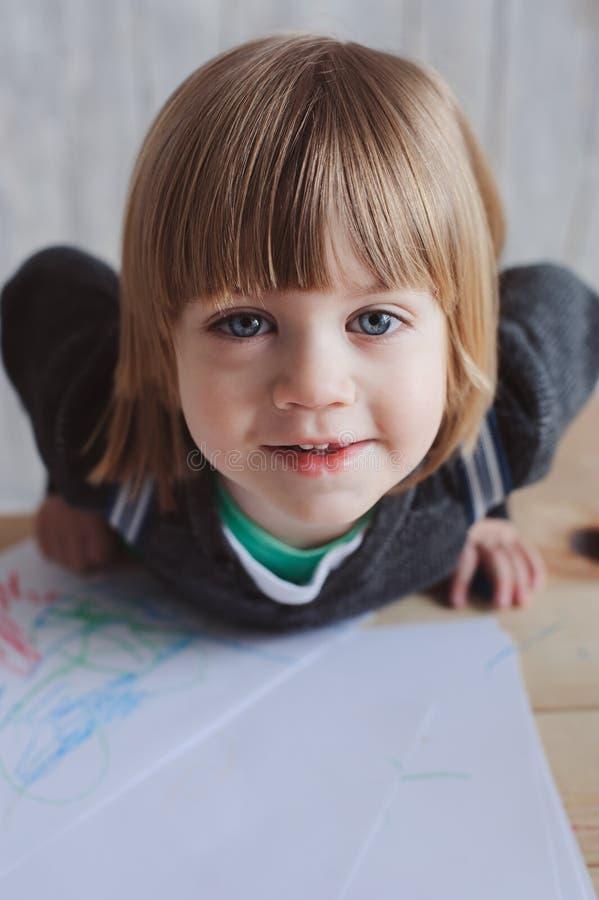 Gullig litet barnpojke som hemma drar arkivfoto