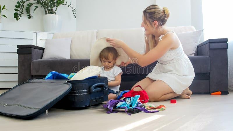 Gullig litet barnpojke som hjälper hans moderemballageting för sommarstrandsemester royaltyfria bilder
