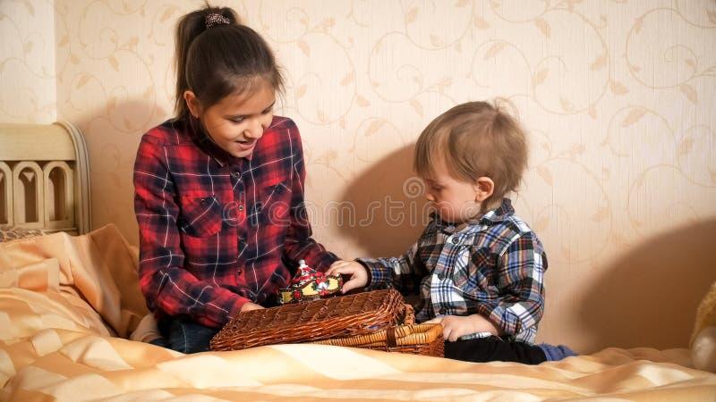 Gullig litet barnpojke som spelar med äldre syster på säng på sovrummet arkivbild