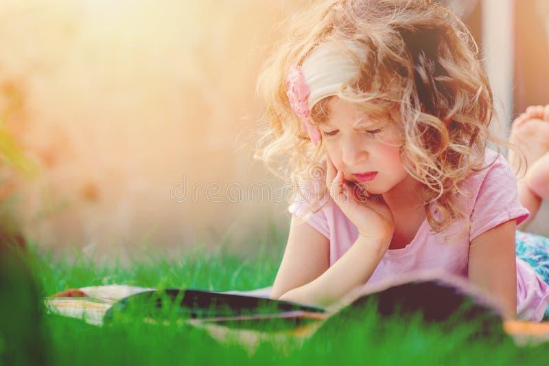 Gullig lockig barnflickaläsebok i sommarträdgård fotografering för bildbyråer