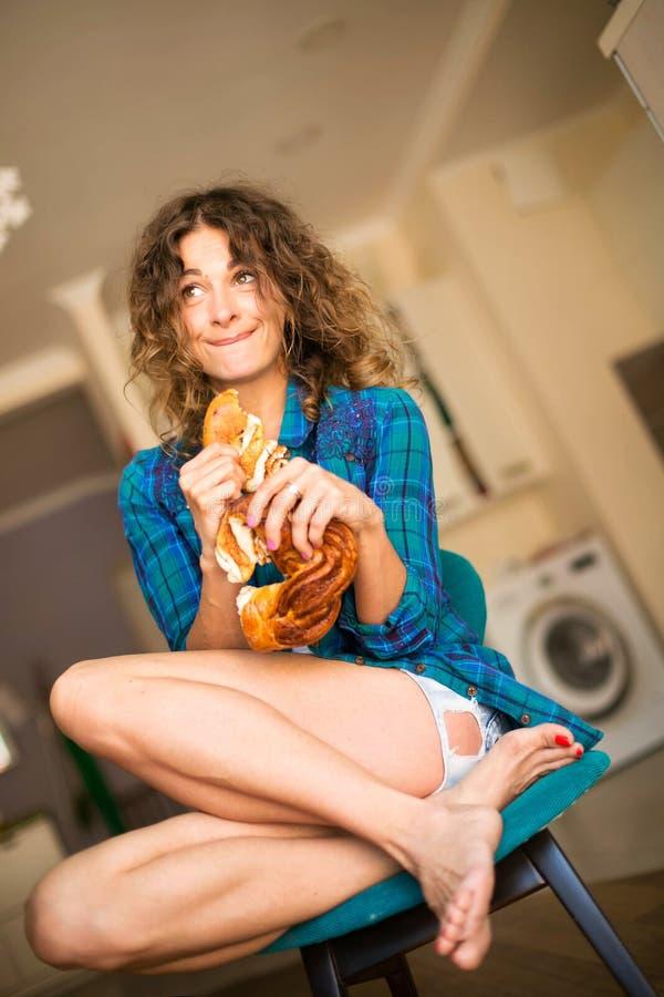 Gullig lockig flicka som äter ett bullesammanträde på en stol i köket royaltyfria bilder