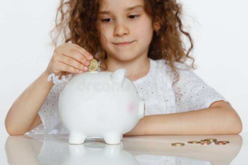 Gullig lockig liten flicka som sätter myntet in i den stora vita spargrisen, över vit bakgrund Bildande sparande pengarbegrepp arkivbilder