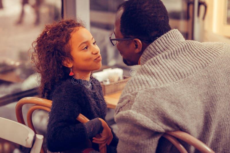 Gullig lockig svartögd dotter som kysser hennes älska fader royaltyfria foton