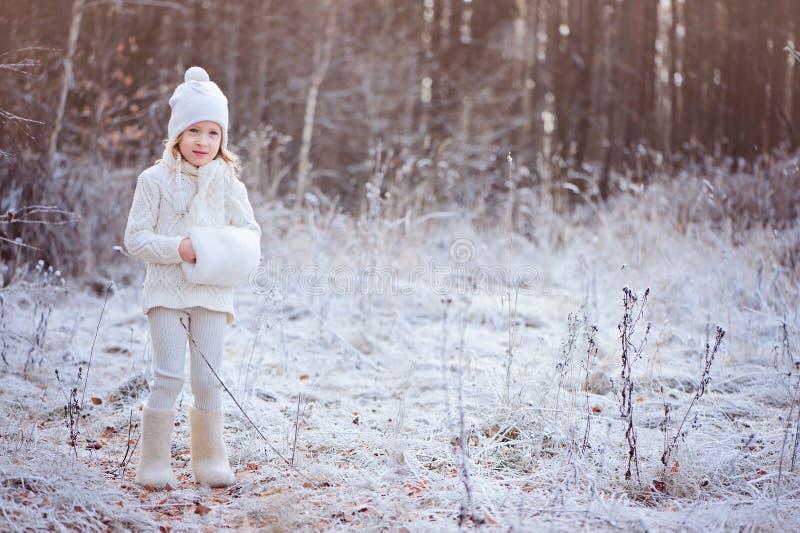Gullig lycklig barnflicka i den vita dräkten som går i djupfryst vinterskog royaltyfria foton