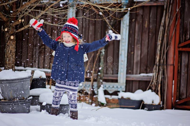 Gullig lycklig barnflicka som har roligt och kastar den insnöade wintergardenen arkivfoton