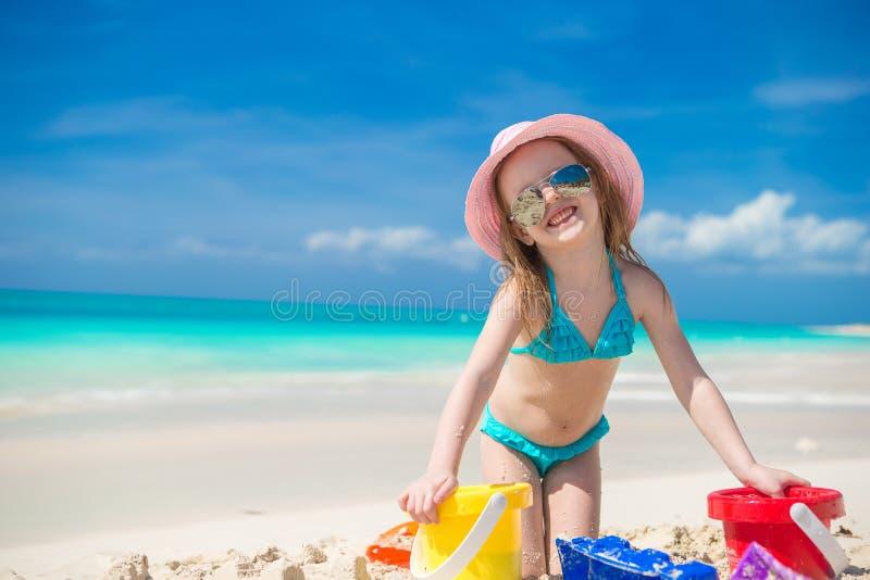 Gullig lycklig flicka som spelar med leksaker på stranden royaltyfri fotografi