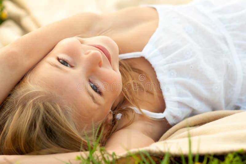 Gullig lycklig liten flicka i vitt ligga för klänning royaltyfri foto