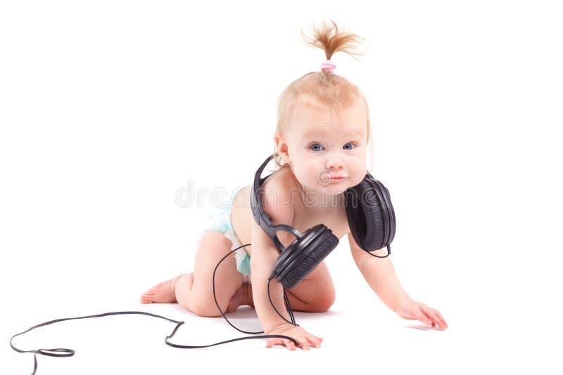 Gullig lycklig liten flicka med hörlurar på hals fotografering för bildbyråer