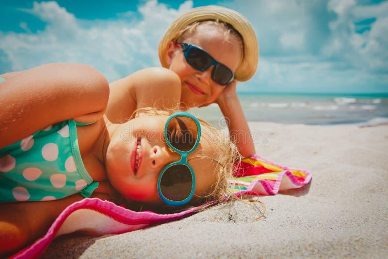Gullig lycklig liten flicka och pojke på den tropiska stranden royaltyfria foton