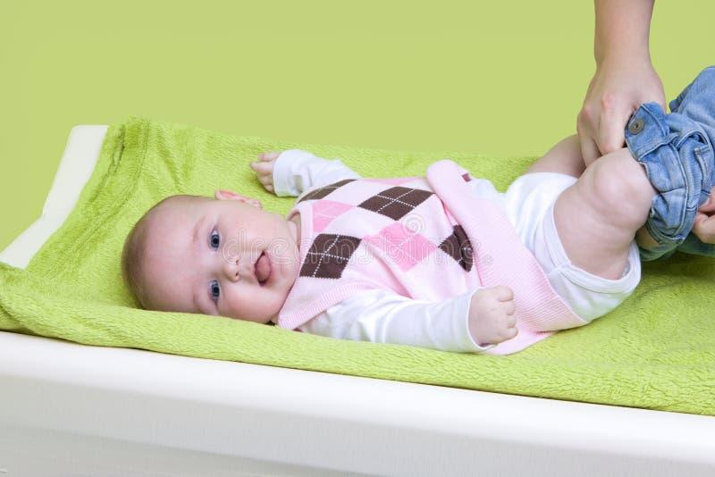 Gullig lycklig liten flicka som får klädd Moder som klär henne för att behandla som ett barn på det ändrande blocket Spädbarnet b royaltyfri foto