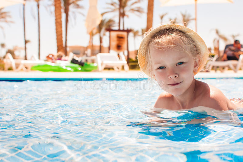 Gullig lycklig liten flicka som har gyckel i simbassäng royaltyfri bild