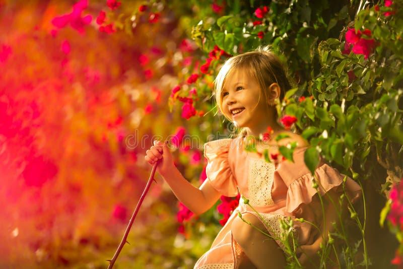 Gullig lycklig liten flicka som poserar med in en parkera royaltyfri foto