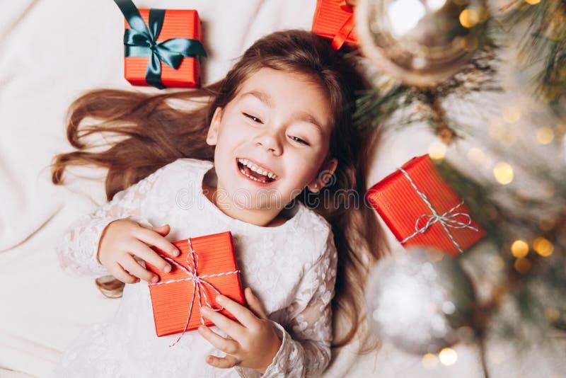 Gullig lycklig liten flicka som skrattar i julatmosfär med gåvaaskar och magiska ljus royaltyfria bilder