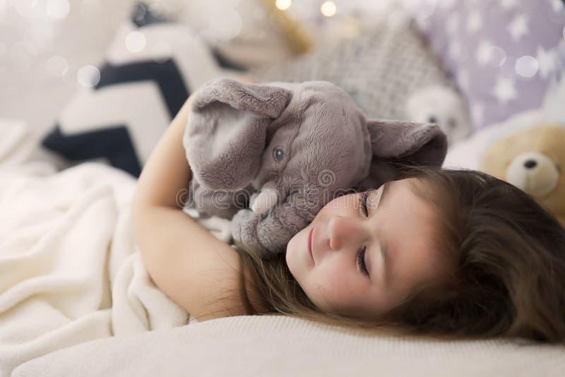 Gullig lycklig liten flicka som in sover och drömmer, och säng som kramar hennes leksak Slut upp fotoet av att sova barnet arkivbild