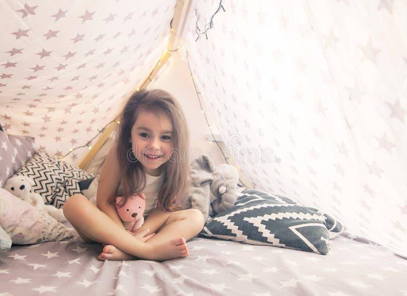 Gullig lycklig liten flicka som spelar med leksaker och drömmer i tipi och säng arkivbild