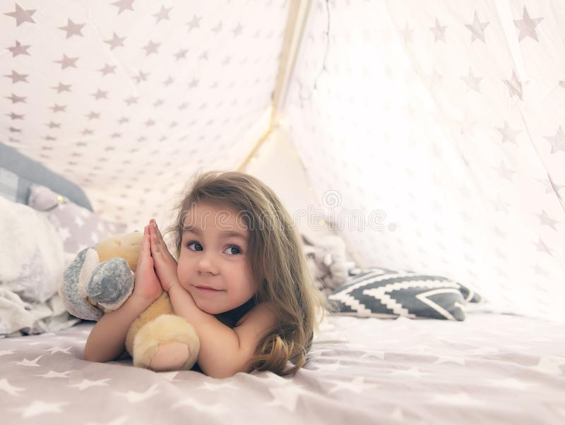 Gullig lycklig liten flicka som spelar med leksaker och drömmer i tipi och säng royaltyfria foton