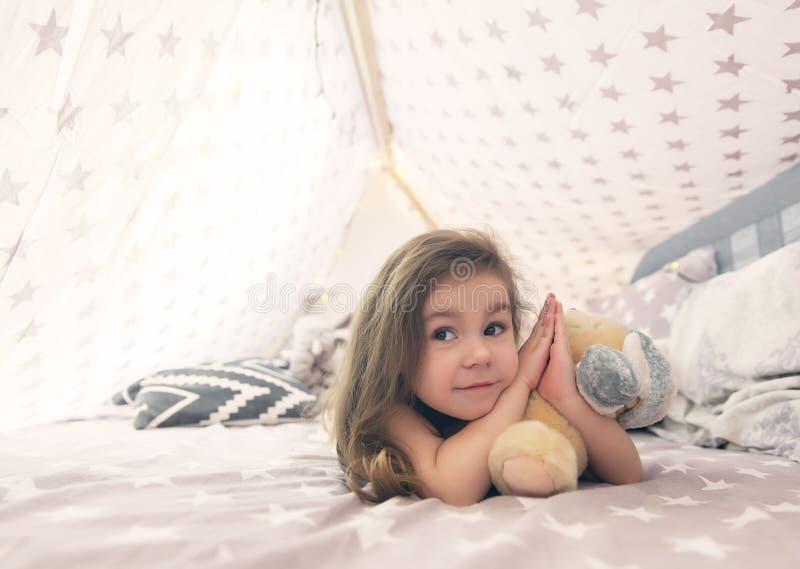 Gullig lycklig liten flicka som spelar med leksaker och drömmer i tipi och säng Slut upp fotoet av det lyckliga barnet arkivfoton