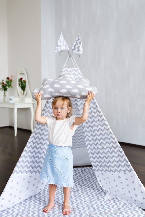 Gullig lycklig liten härlig flicka med kuddeanseende i tipi på barnkammarerum arkivbild