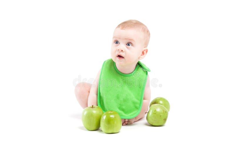 Gullig lycklig pys i near gröna äpplen för grön haklapp fotografering för bildbyråer