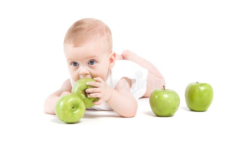 Gullig lycklig pys i near gröna äpplen för vit skjorta royaltyfri foto