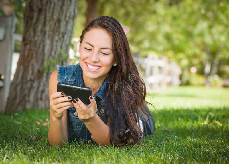 Gullig lycklig tonårig kvinnlig för blandat lopp som smsar på hennes smarta telefon royaltyfri bild