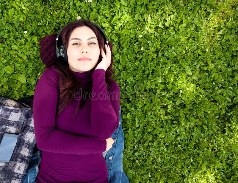 Gullig lyssnande musik f?r ung kvinna med h?rlurar arkivfoton