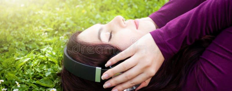 Gullig lyssnande musik f?r ung kvinna med h?rlurar royaltyfri foto