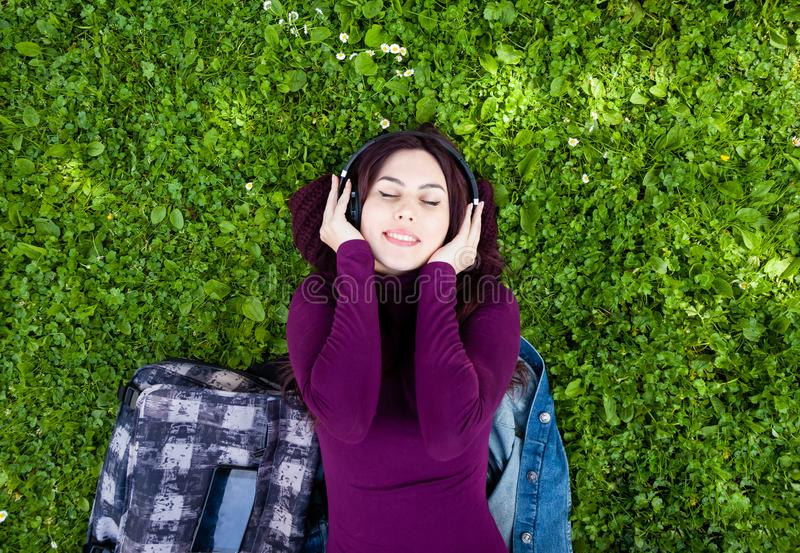 Gullig lyssnande musik f?r ung kvinna med h?rlurar arkivfoto
