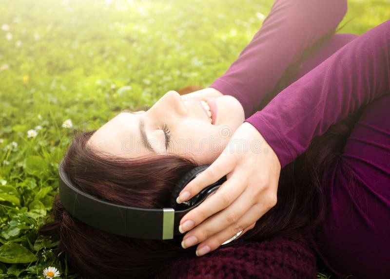 Gullig lyssnande musik f?r ung kvinna med h?rlurar fotografering för bildbyråer