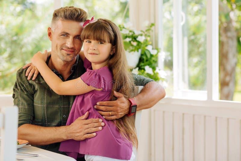 Gullig mörker-haired dotter som kramar hennes älska stiliga pappa arkivfoto