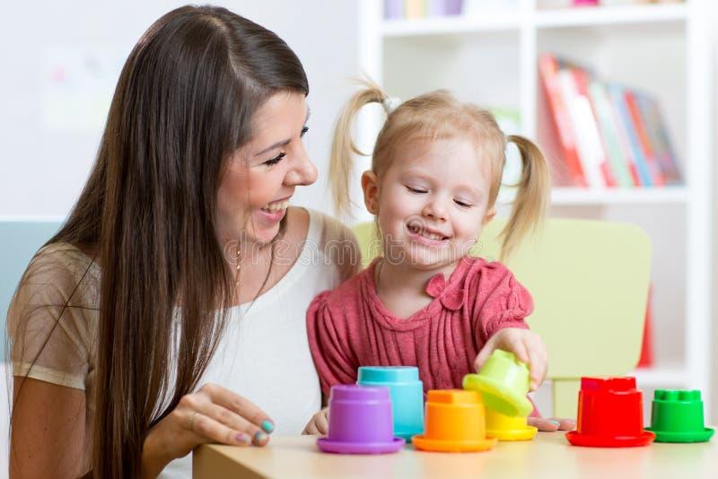 Gullig moder- och barndotter som spelar bildande leksaker inomhus royaltyfri fotografi