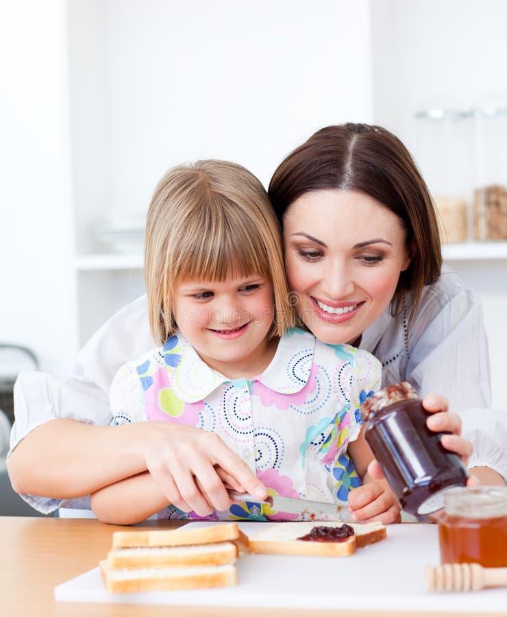 Gullig moder som hjälper henne dotter i kök arkivbild