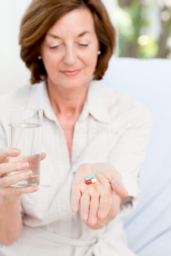 Gullig mogen kvinna med pills 免版税图库摄影