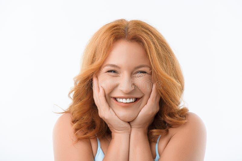 Gullig mogen kvinna som lyckligt skrattar arkivbild