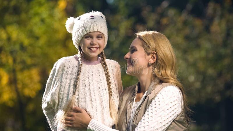 Gullig mum och dotter som poserar för kamera som tillsammans spenderar tid utomhus, nedgång royaltyfri foto