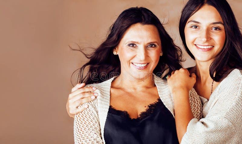 Gullig nätt tonårig dotter med den mogna modern som kramar, modest royaltyfri fotografi