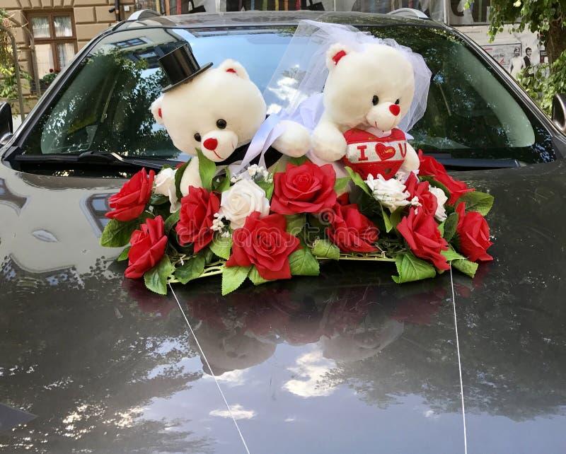 Gullig nallebjörn som gifta sig prydnaden på en bil arkivbilder