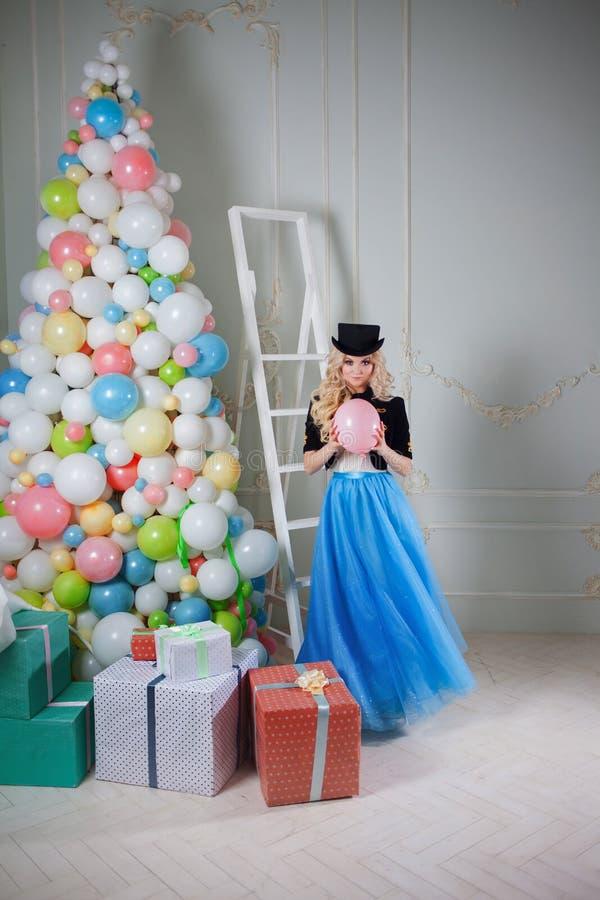Gullig och härlig blondin nära julgranen av ballons och gåvor i askar Den charmiga unga kvinnan i en curvy blått kringgår arkivfoto