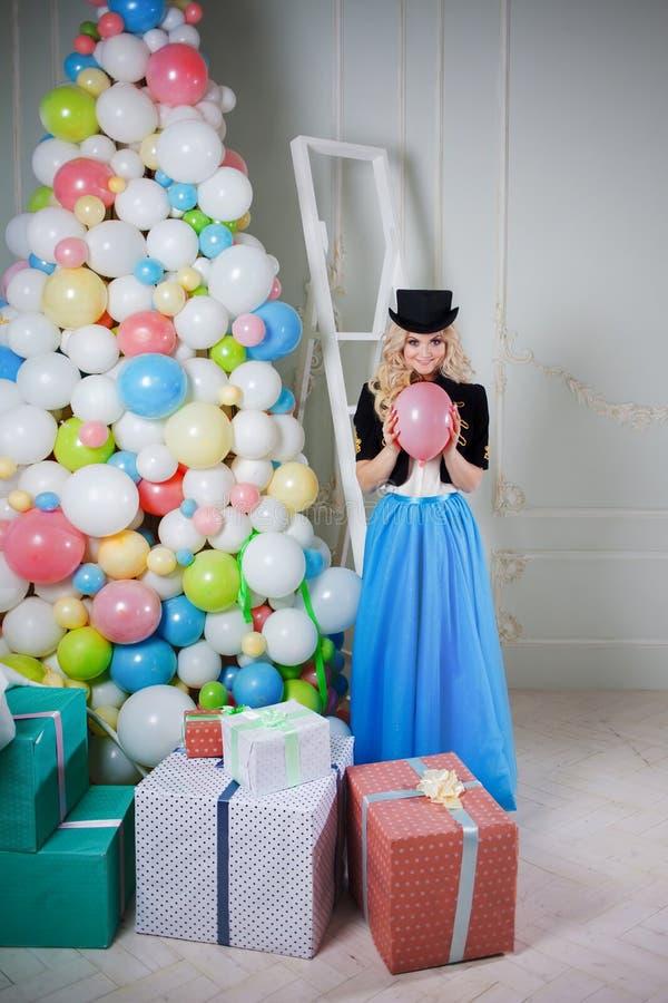 Gullig och härlig blondin nära julgranen av ballons och gåvor i askar Den charmiga unga kvinnan i en curvy blått kringgår arkivbild