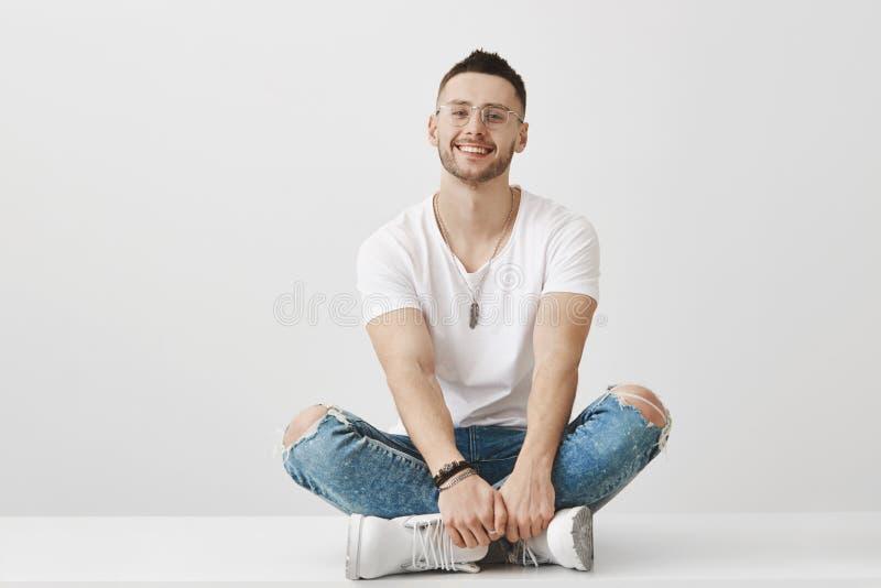 Gullig och moderiktig pojkvän i exponeringsglas som sitter på golv med korsade ben och att rymma händer på fot som i huvudsak ler royaltyfri foto
