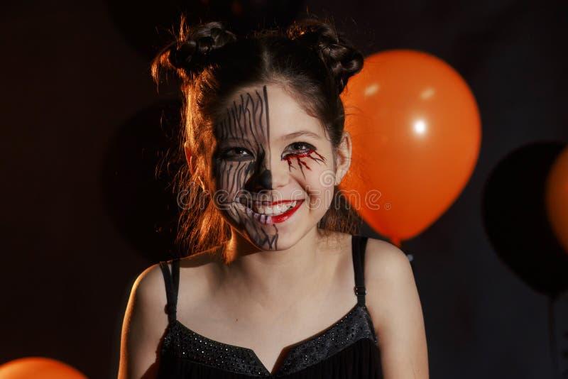Gullig och nätt flicka med lång krullning som poserar för halloween som bär en enorm svart- och apelsinhatt royaltyfri foto