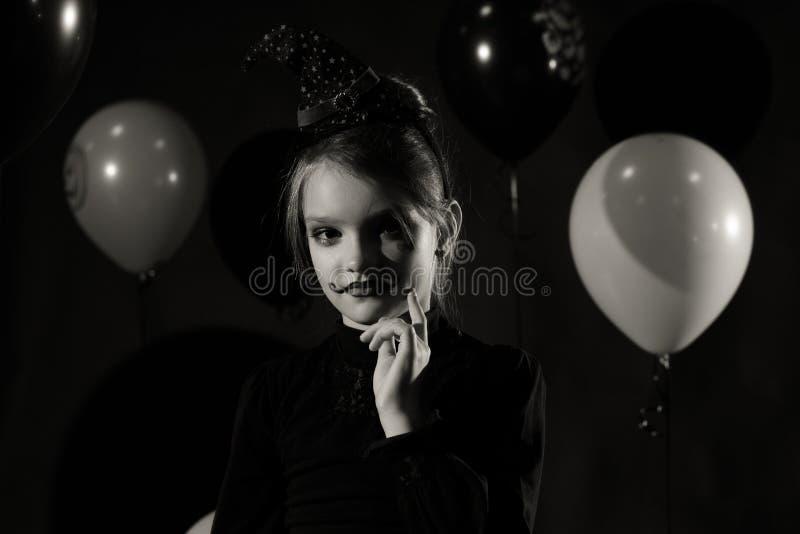 Gullig och nätt flicka med lång krullning som poserar för halloween som bär en enorm svart- och apelsinhatt royaltyfria foton