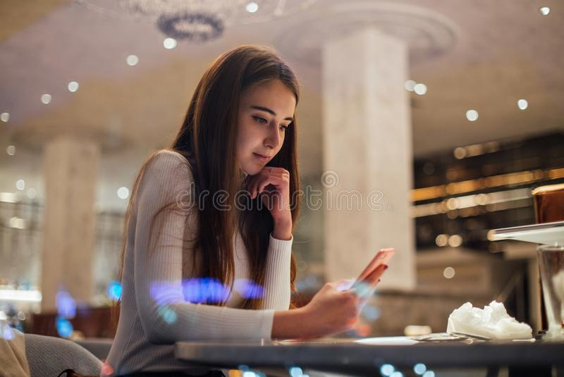 Gullig och nätt ung kvinna på smartphonen i kafé arkivbild