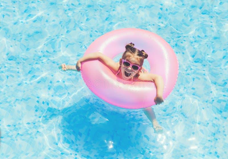 Gullig och rolig flicka i simbassäng royaltyfri fotografi